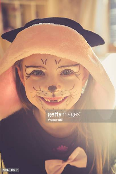 Portrait of smiling little girl with tooth gap masquerade as a cat