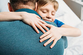 portrait of smiling little son hugging father in hospital chamber