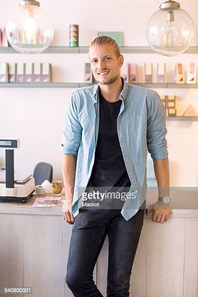 Portrait of smiling male owner standing candy store