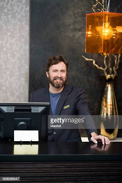 Portrait of smiling male receptionist standing at counter in hotel