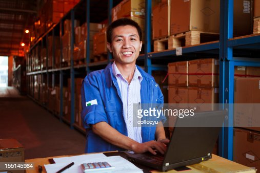 Portrait of smiling male warehouse worker using a laptop