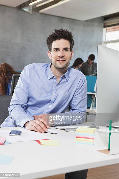 Portrait of smiling man at his workplace in the office