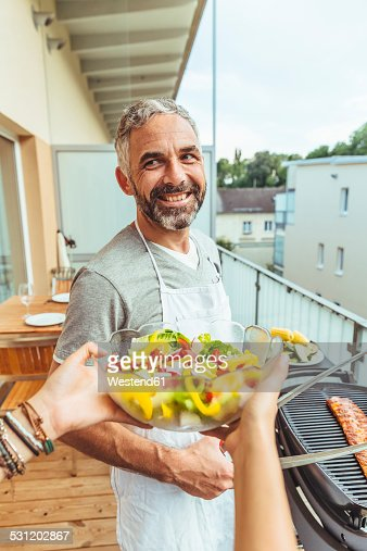 Portrait of smiling man barbecuing on his balcony with womans hands holding salad bowl in the foreground
