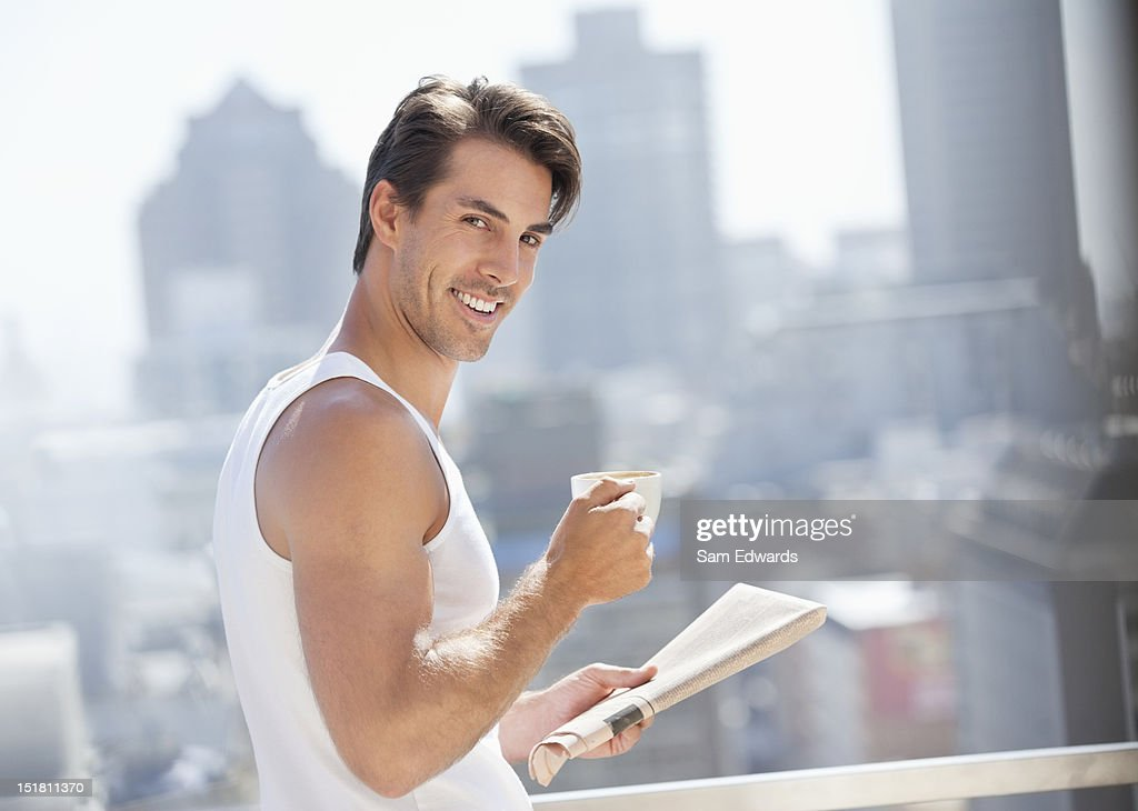 Portrait of smiling man drinking coffee and reading newspaper on urban balcony : Stock Photo