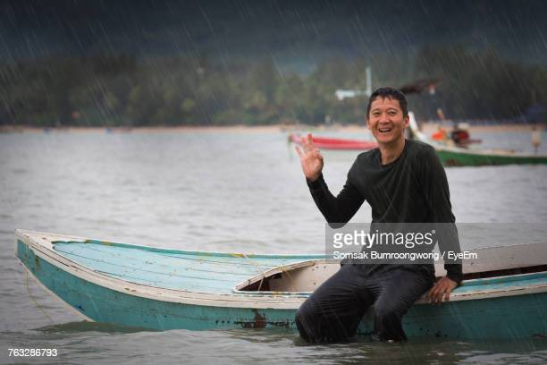 Portrait Of Smiling Man Gesturing While Sitting On Boat In Sea During Rainy Day