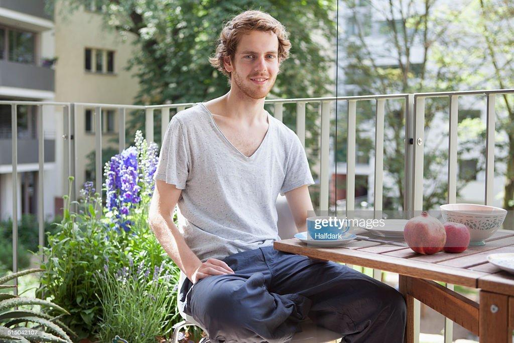 Portrait of smiling man having breakfast at porch