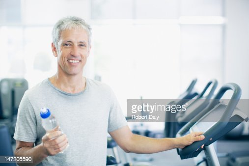Portrait of smiling man holding water bottle on treadmill in gymnasium : Stock Photo