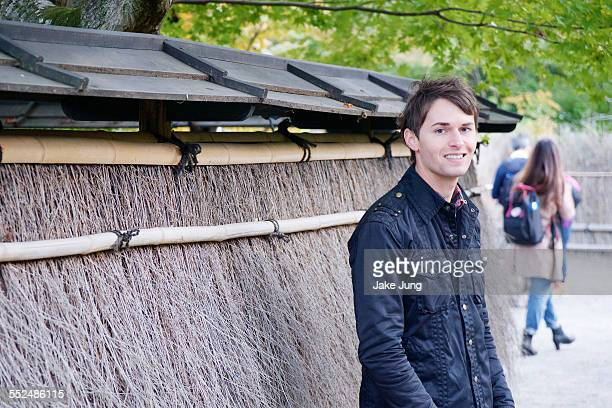 Portrait of smiling man in front of straw fence