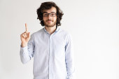 Portrait of smiling man in glasses showing forefinger. Young Caucasian man wearing shirt showing attention or idea sign. Solution concept