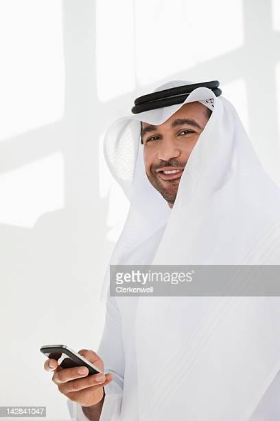 Portrait d'homme souriant dans Keffieh avec téléphone portable