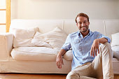 Portrait of smiling man leaning against sofa