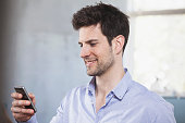 Portrait of smiling man looking at his smartphone