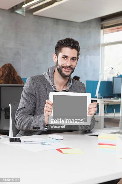Portrait of smiling man showing tablet computer in the office