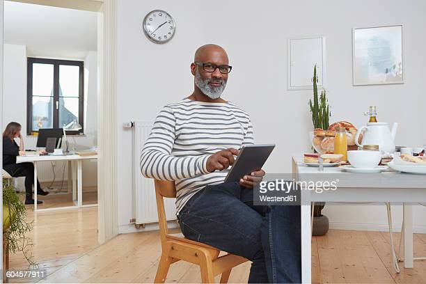 Portrait of smiling man sitting at breakfast table with digital tablet