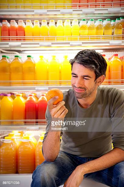 Portrait of smiling man sitting in front of fridge with rows of juice bottles in a supermarket holding an orange