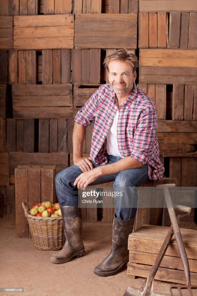 Portrait of smiling man sitting next to bushel of apples