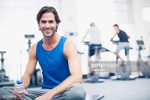 Porträt eines lächelnden Mann sitzt auf der Matte Training im Fitnessraum