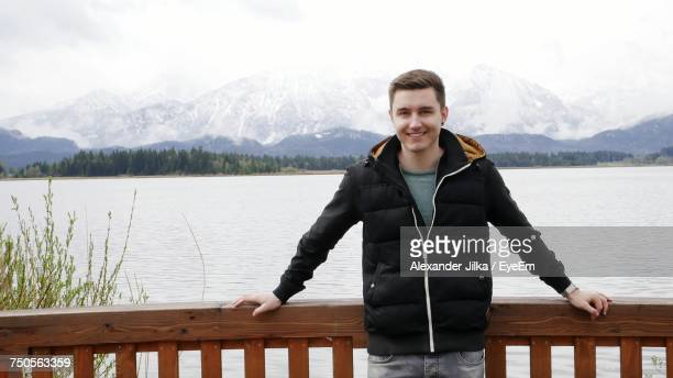 Portrait Of Smiling Man Standing By Railing Against Lake And Mountains