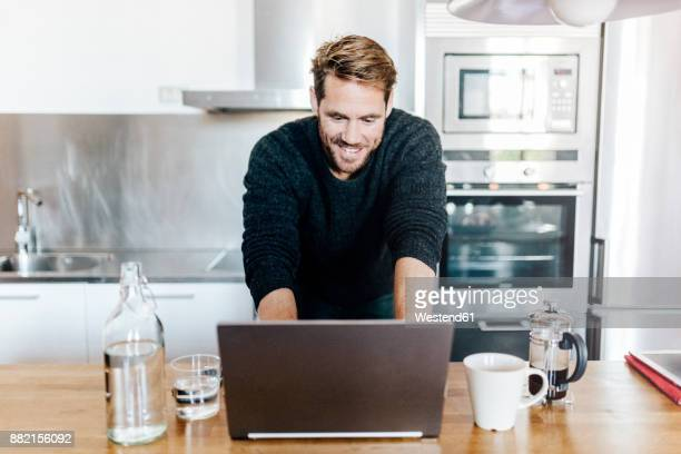 Portrait of smiling man standing in kitchen using laptop
