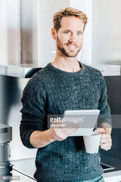 Portrait of smiling man standing in kitchen with tablet and coffee mug