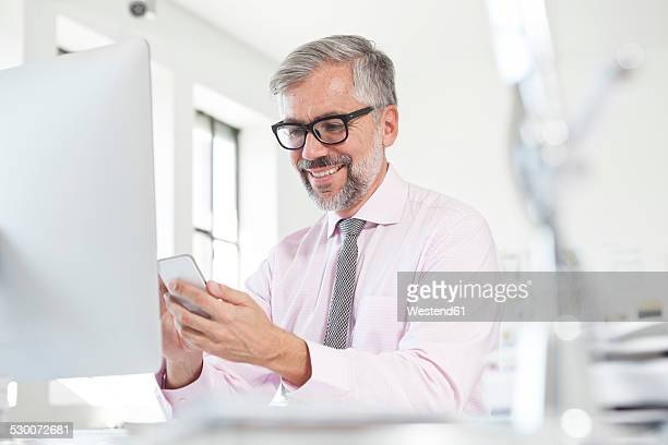 Portrait of smiling man using smartphone at his desk in an office