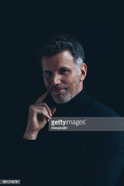Portrait of smiling man wearing black turtleneck in front of black background