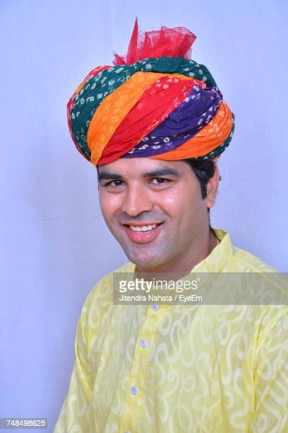 Portrait Of Smiling Man Wearing Colorful Turban Against Wall