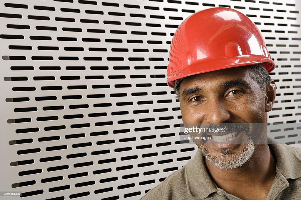 Portrait of smiling man wearing hardhat : Stock Photo