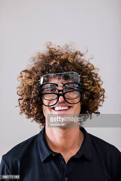 Portrait of smiling man with curly hair wearing four different glasses