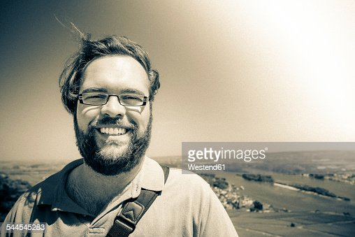 Portrait of smiling man with full beard wearing glasses