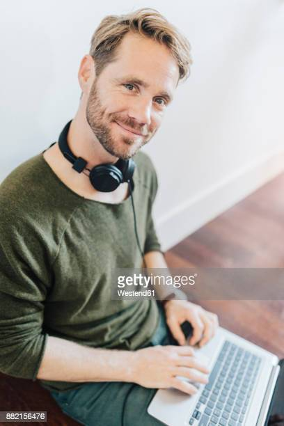 Portrait of smiling man with headphones and laptop