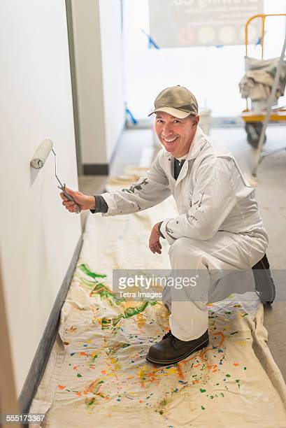Portrait of smiling manual worker painting wall