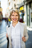 Portrait of positive smiling mature blond woman walking in town