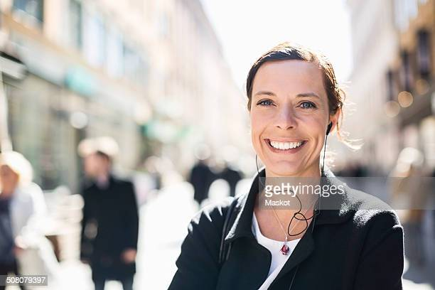 Portrait of smiling mature businesswoman listening to music on city street