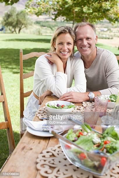 Porträt von lächelnd Älteres Paar mit Frühstückstisch in lawn