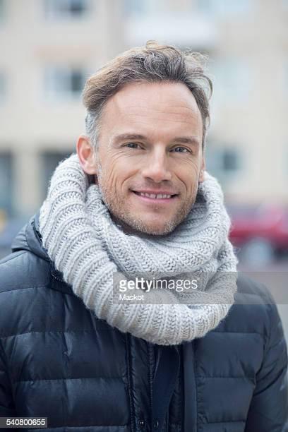 Portrait of smiling mature man on street against building