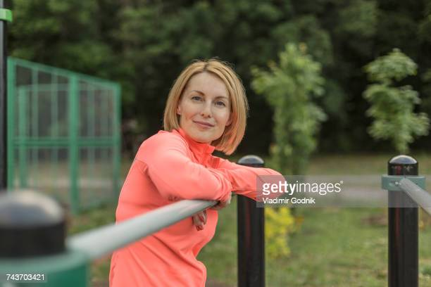 Portrait of smiling mature woman leaning on railing against trees at park