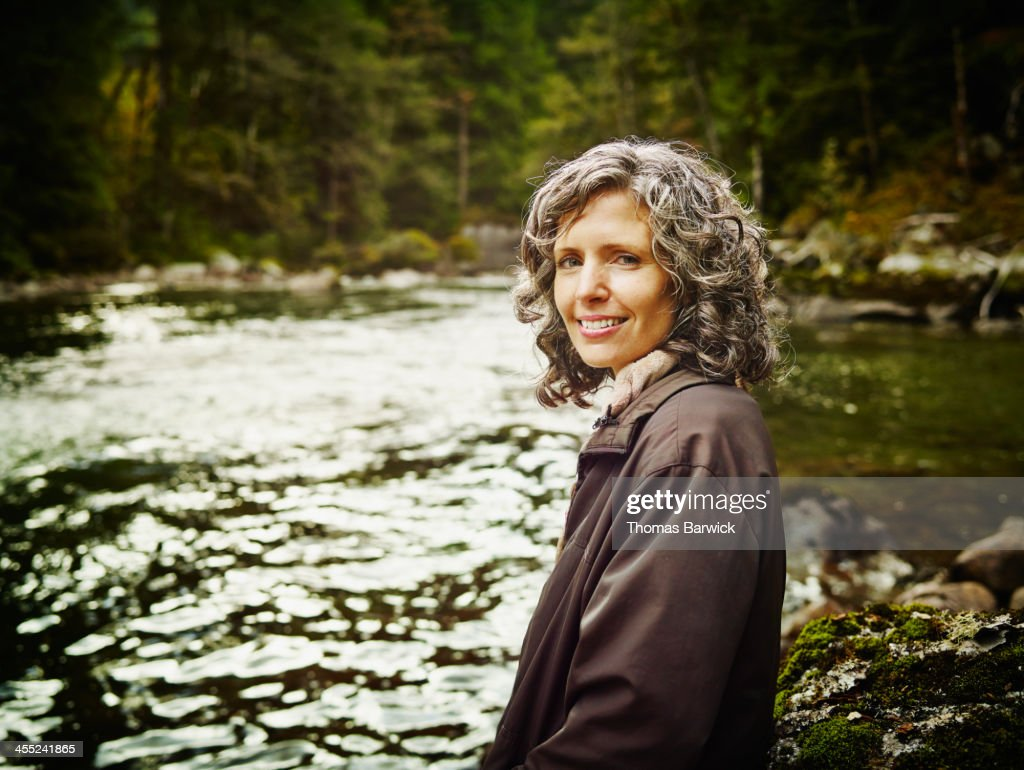 Portrait of smiling mature woman near river : Stock Photo