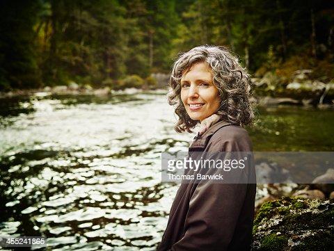 Portrait of smiling mature woman near river : Stock Photo