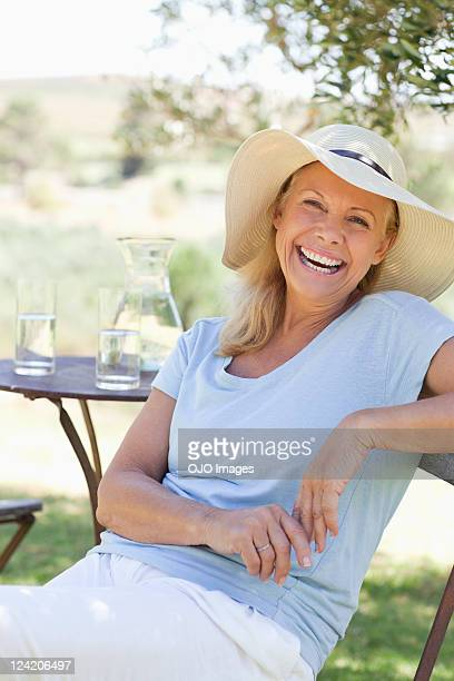 Portrait of smiling mature woman sitting in chair at the lawn