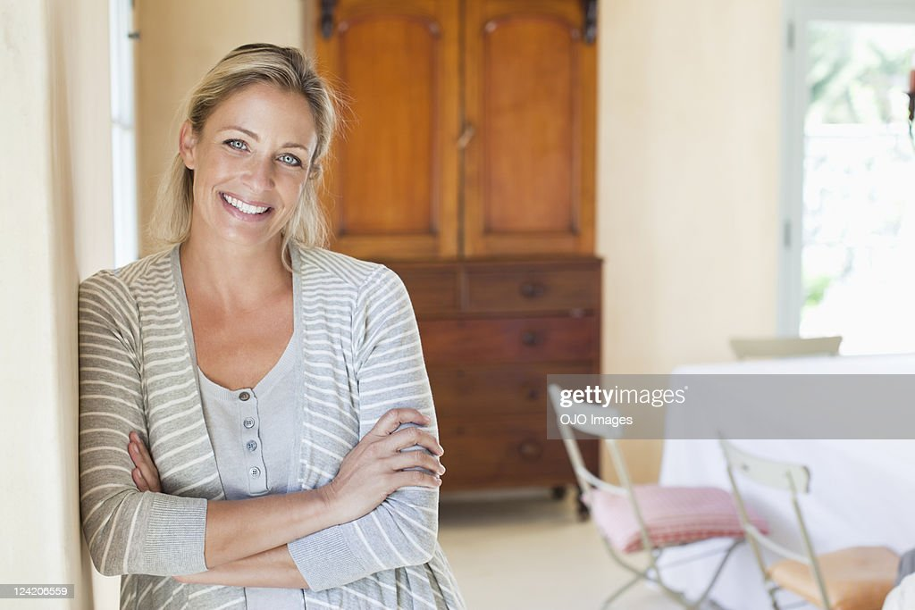 Portrait of smiling mature woman standing in living room : Stock Photo
