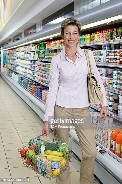 Portrait of smiling mature woman with shopping basket in supermarket
