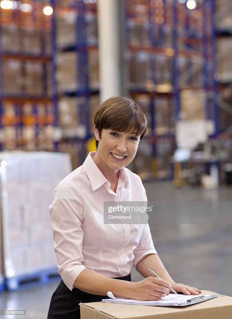 Portrait of smiling mature woman working in warehouse : Stock Photo