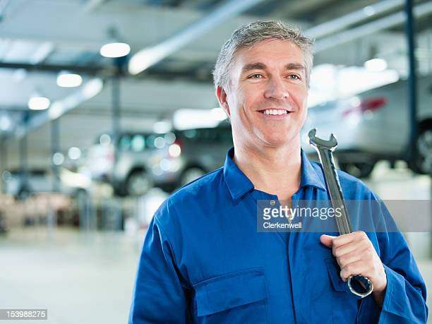 Portrait of smiling mechanic holding large wrench in auto repair shop