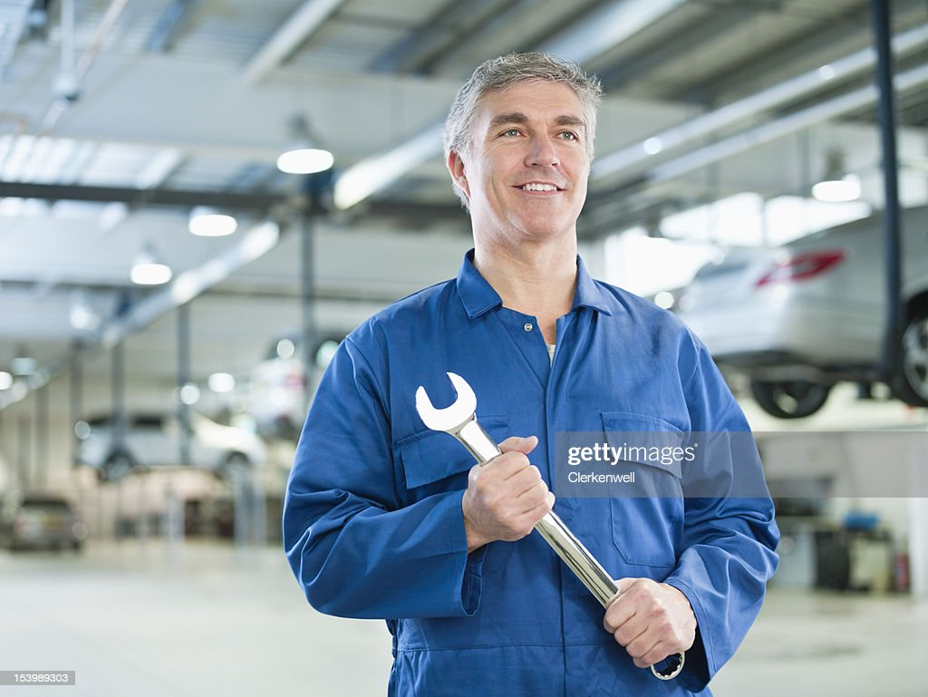 Portrait of smiling mechanic holding large wrench in auto repair shop : Stock Photo