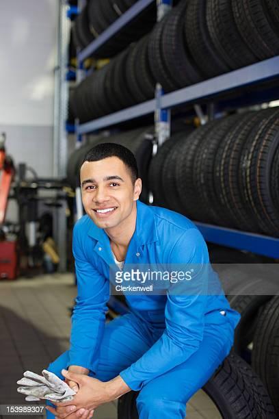 Ritratto di un sorridente meccanico seduti su pneumatici per auto