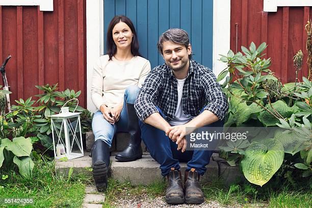 Portrait of smiling mid adult couple sitting outside farmhouse