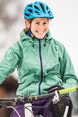 Portrait of smiling mid adult female mountain biker on bike