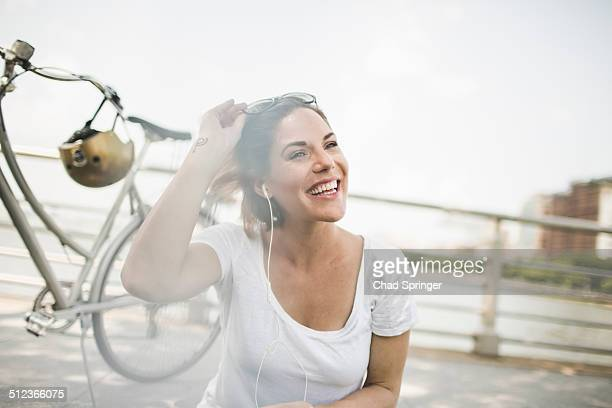 Portrait of smiling mid adult woman cyclist listening to earphones