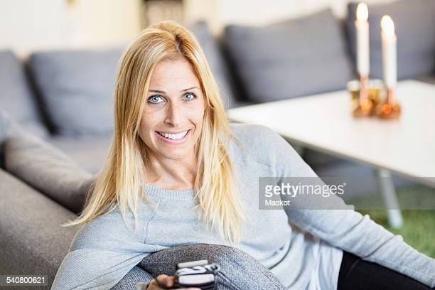 Portrait of smiling mid adult woman using smart phone at home
